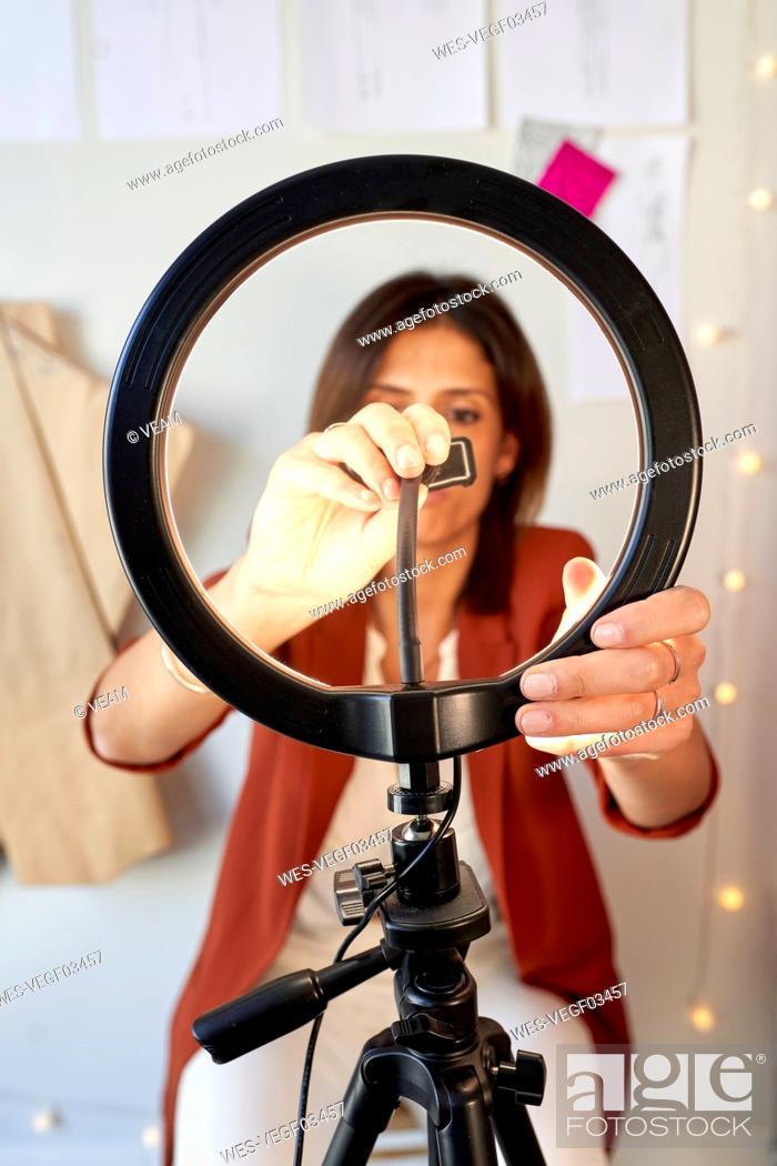 Stock Photo: Female fashion designer adjusting circle light for vlogging at atelier.