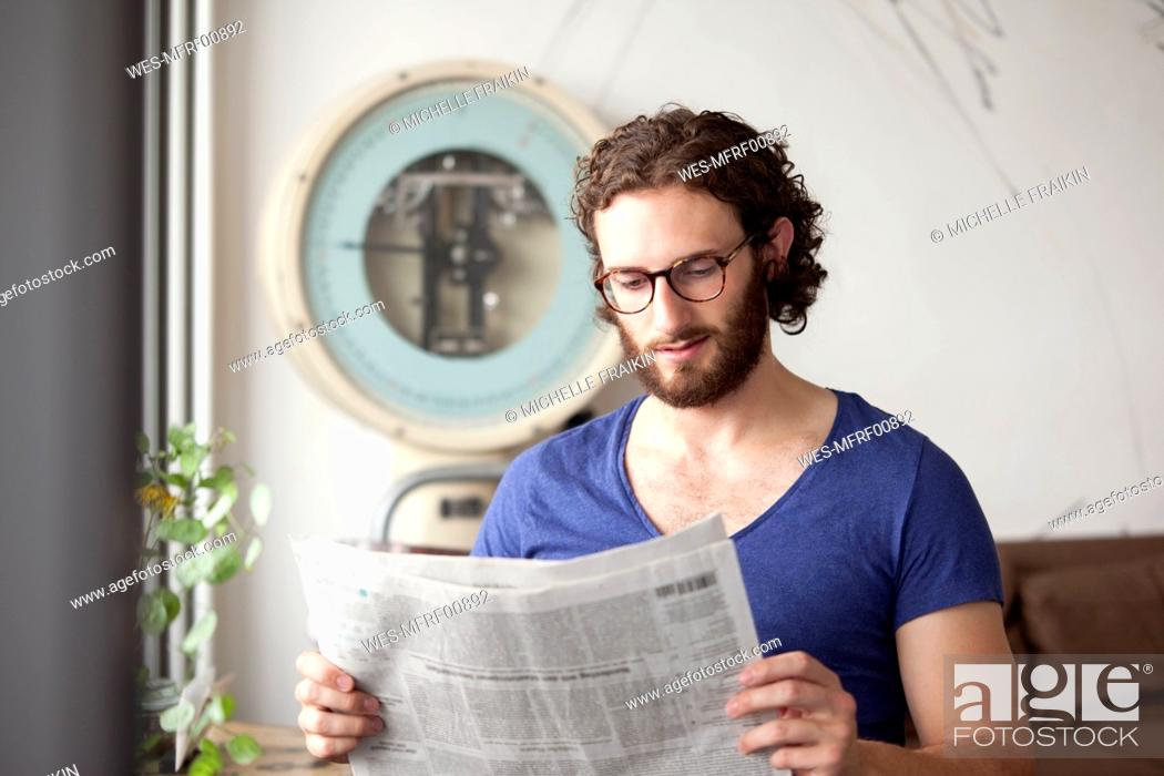 Stock Photo: Portrait of young man reading newspaper in a coffee shop.
