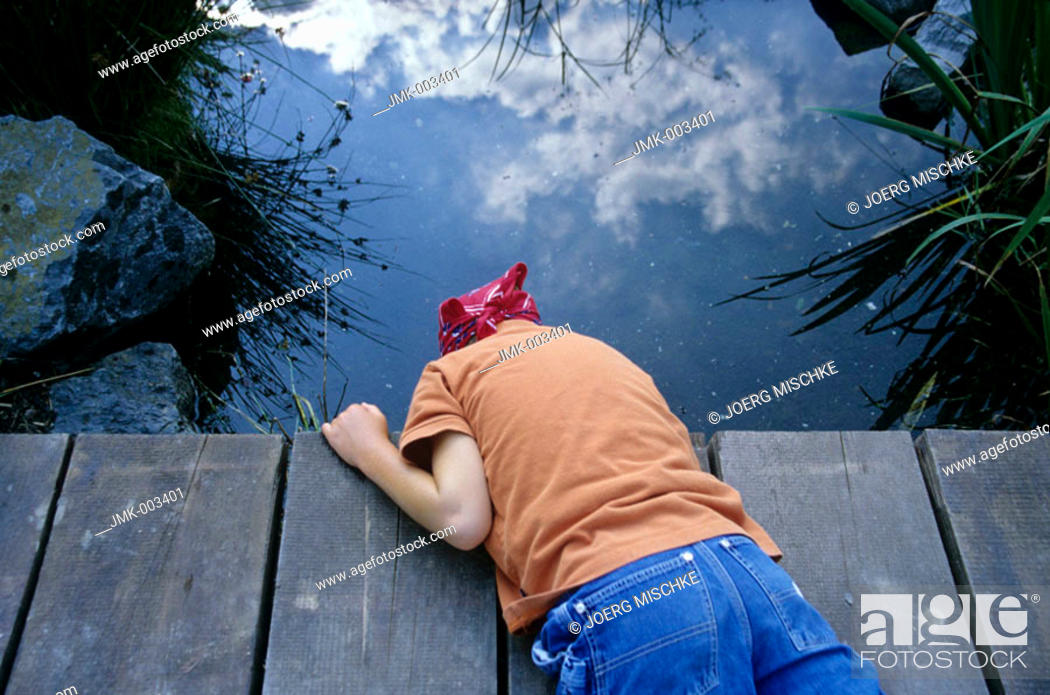 Stock Photo: A boy, 5-10 years old, lying on a footbridge, looking into the water of a pond outside in the garden in summer.