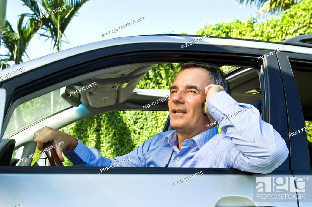Stock Photo: Man in a car and talking on a mobile phone.