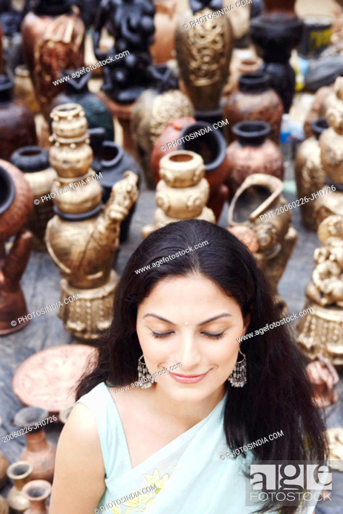 Stock Photo: High angle view of a young woman standing with her eyes closed in a pottery store.