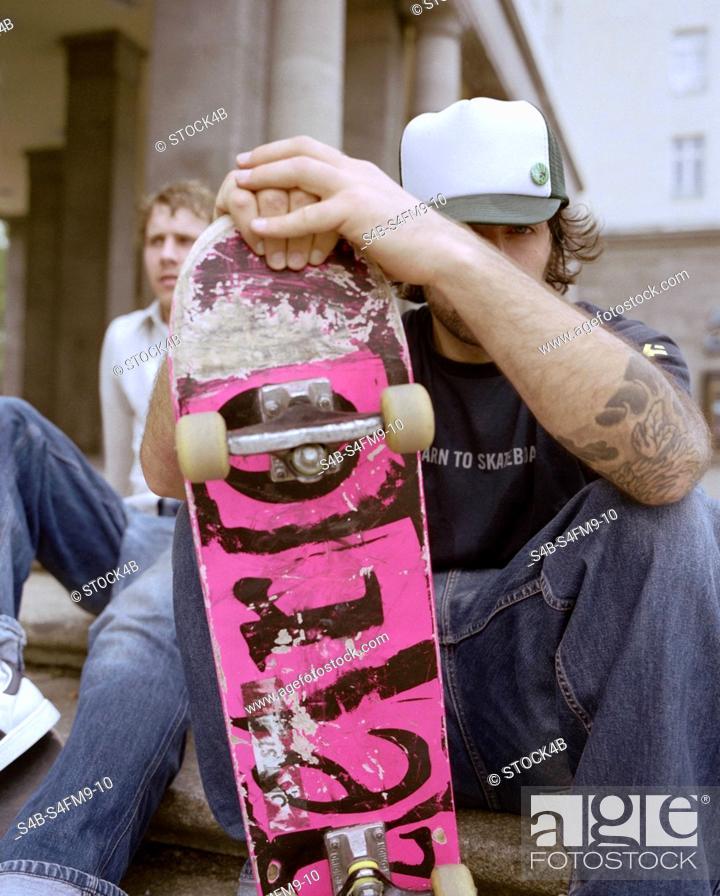 Stock Photo: Two sitting Skateboarders - Skateboarding.