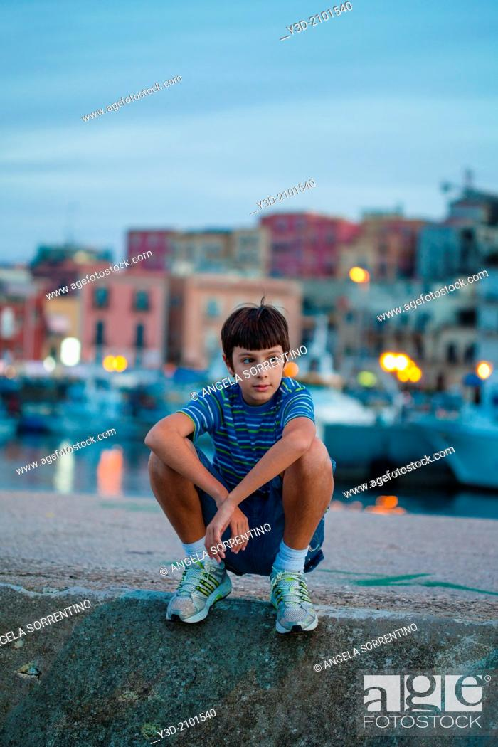 Imagen: Young boy at evening on harbor of Naples, Italy.