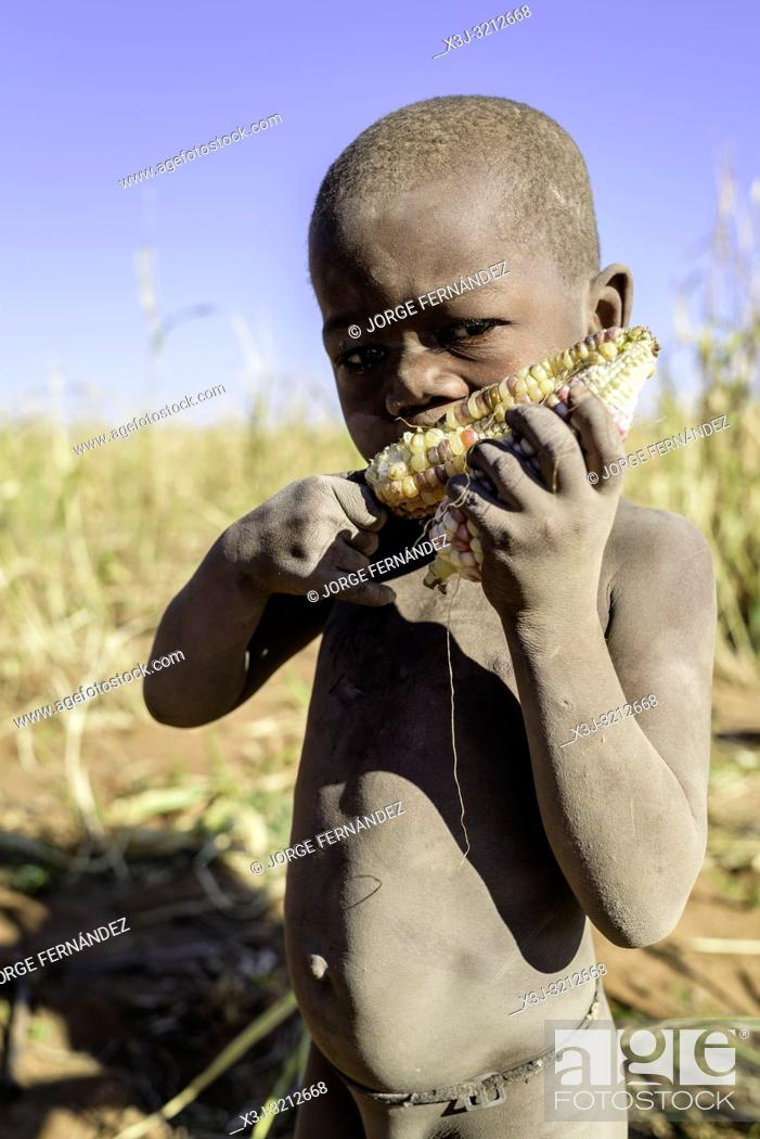 Stock Photo: Portrait of a naked Himba boy eating a corncob.