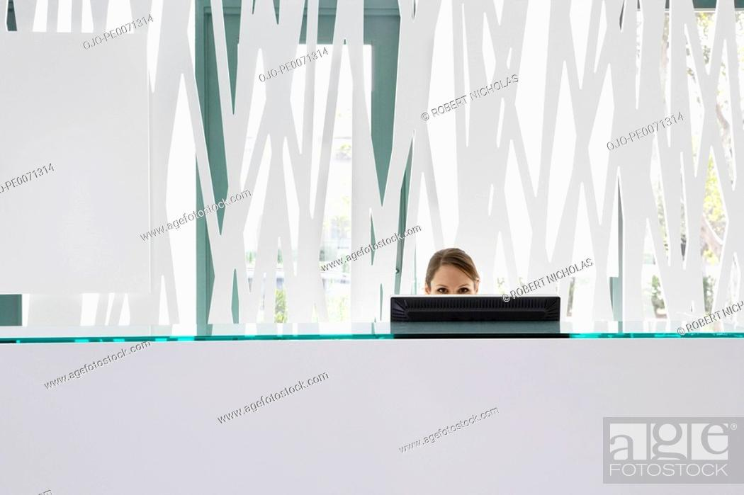 Stock Photo: Businesswoman working on computer at reception desk.