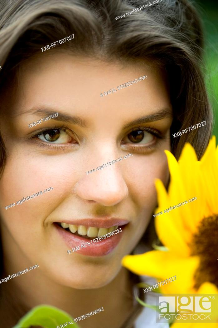 Stock Photo: Young woman with sunflowers.