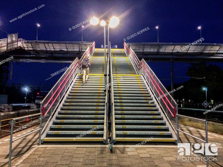 Stock Photo: Breda, Netherlands. Stairs to an overhead traverse over the track at central railway station Breda, Netherlands, at night.