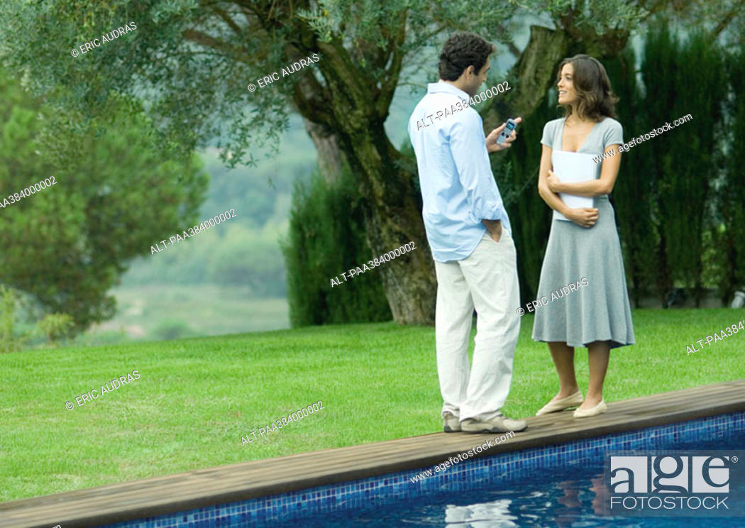 Stock Photo: Man and woman standing near edge of pool with documents and cell phone.