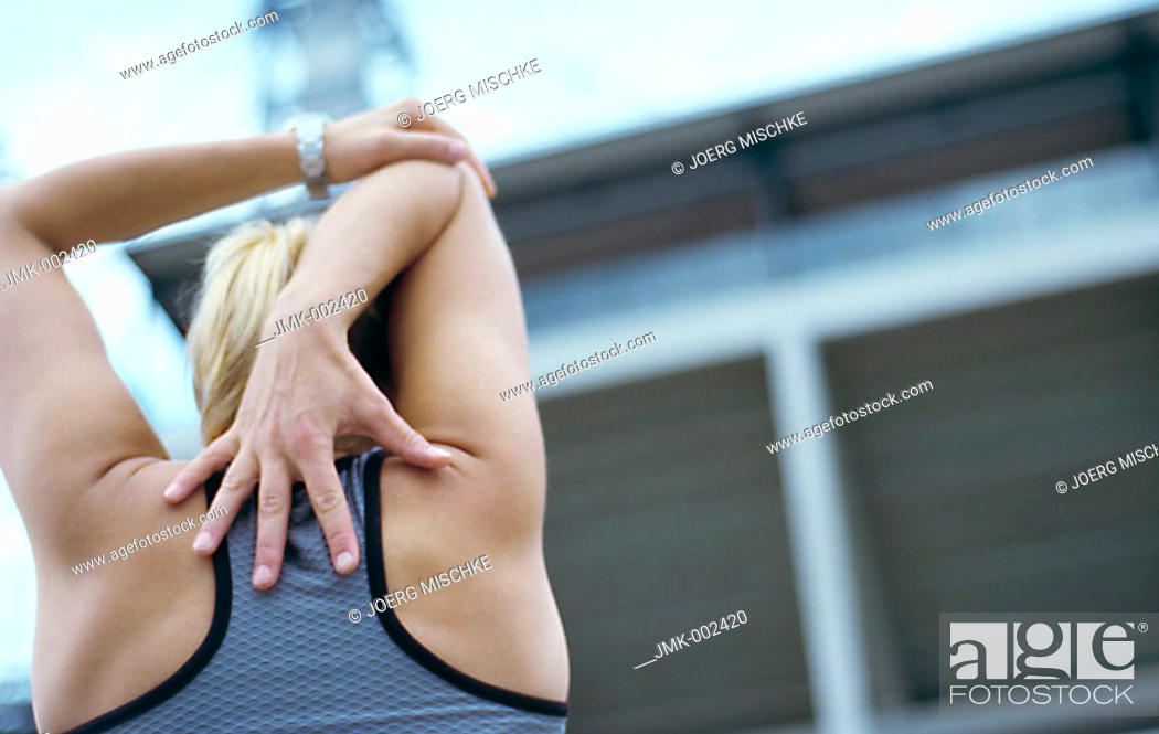 Stock Photo: A young athletic woman, 15-20 20-25 25-30 years old, blond, sporty, stretching.
