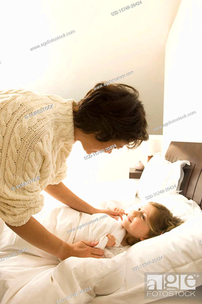 Stock Photo: Side profile of a young woman bending over her daughter lying on the bed.