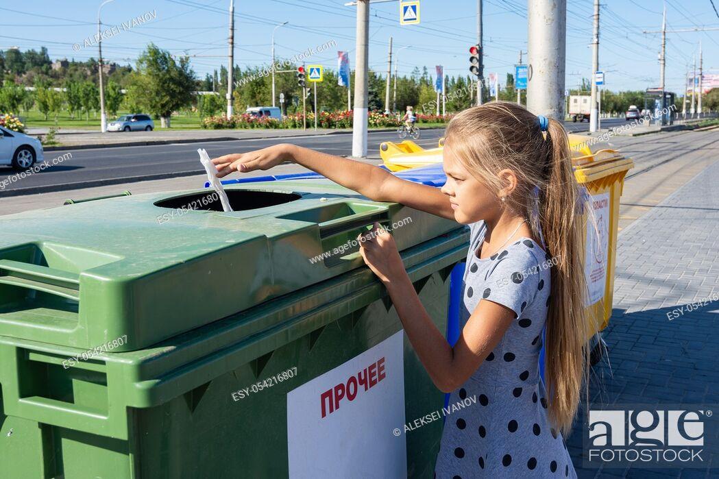 Stock Photo: Girl throws a napkin into the trash bin.
