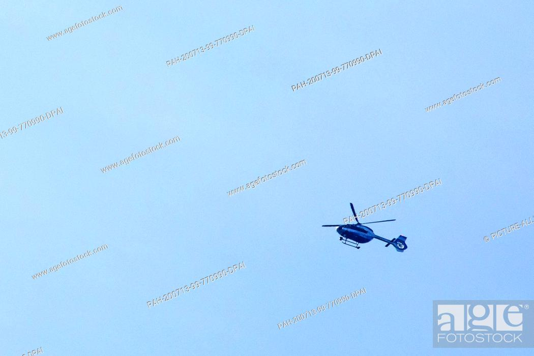 Stock Photo: 13 July 2020, Baden-Wuerttemberg, Oppenau: A police helicopter flies over the forest near the community of Oppenau. A large police contingent has been searching.
