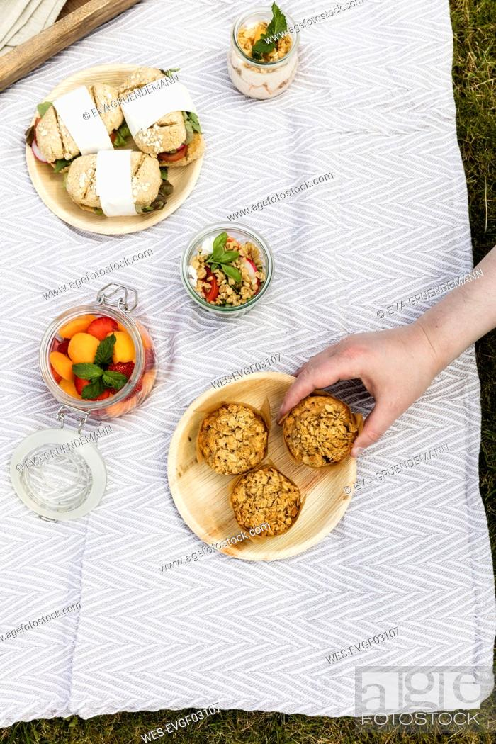 Stock Photo: Hand taking muffin from picnic blanket with vegetarian snacks.