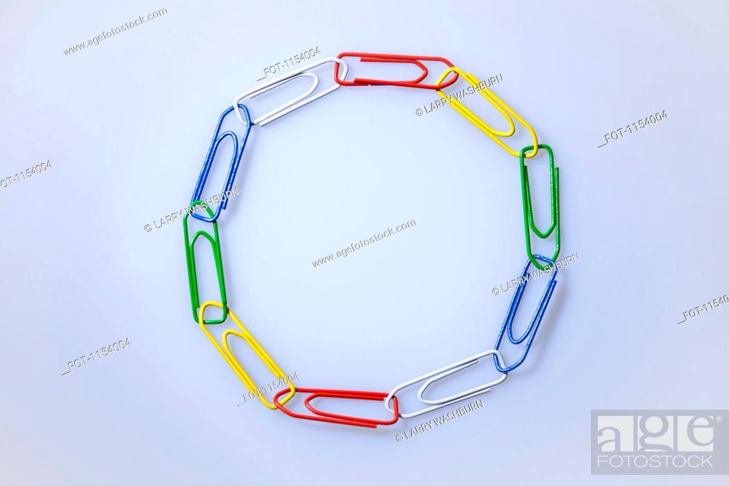 Stock Photo: Multi colored paperclips arranged in a circle.