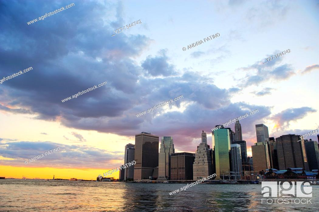 Stock Photo: Sunset behind the Downtown Manhattan Skyline and the New York Harbor.