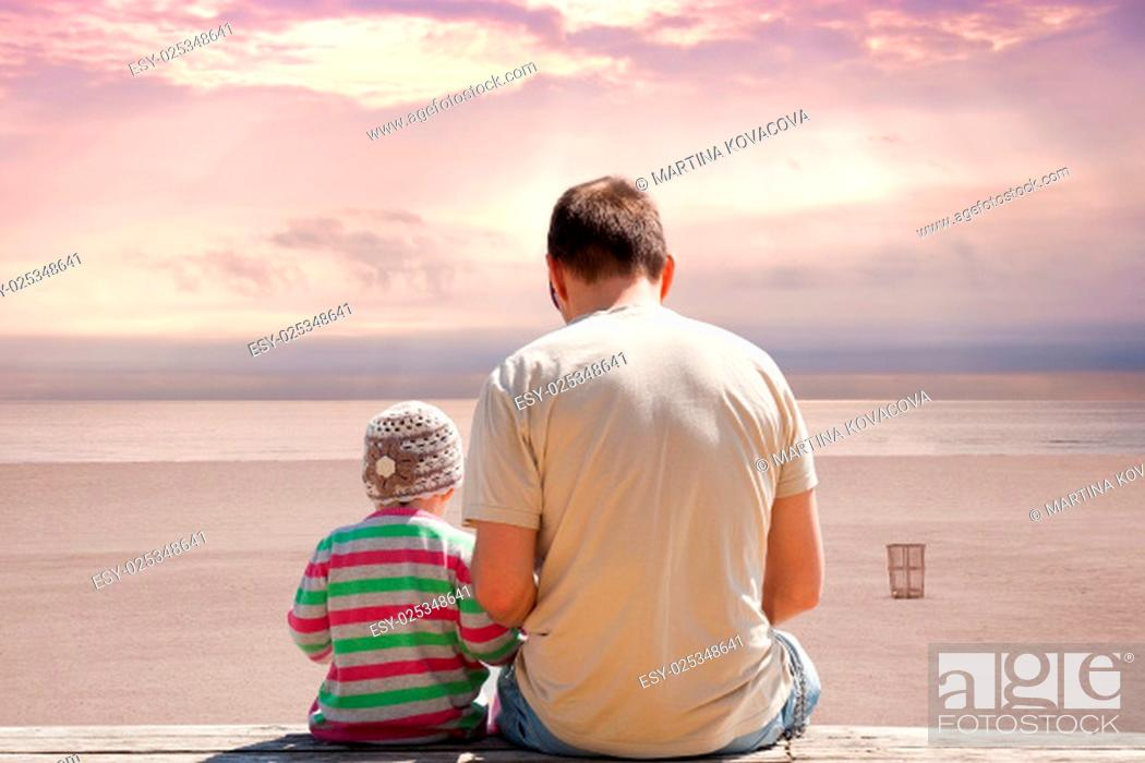 Imagen: Father and daughter sitting on bench on empty beach at sunset with dramatic atmospheric clouds. Miami Beach Florida, USA.