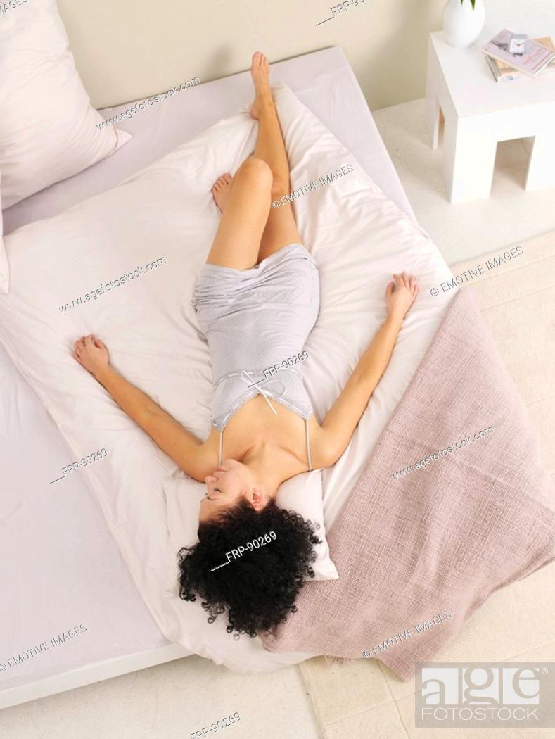 Stock Photo: young woman streched out on the bed.