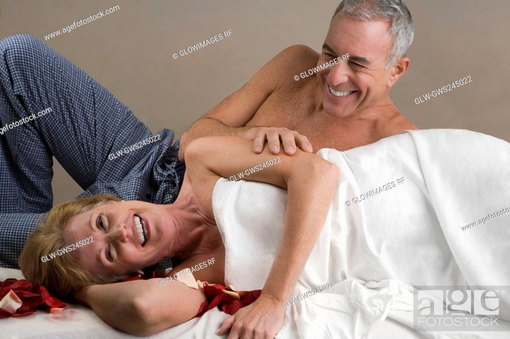 Stock Photo: Mature woman with a senior man lying on a massage table and smiling.