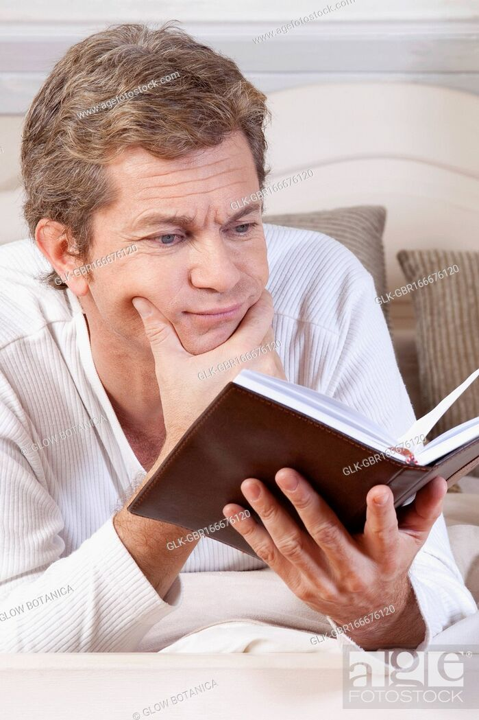 Stock Photo: Man reading a book on the bed.