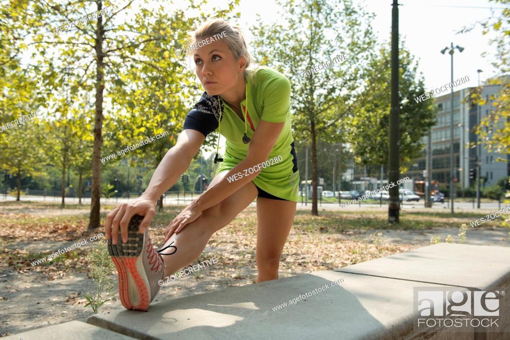 Stock Photo: Female athlete stretching in urban park.