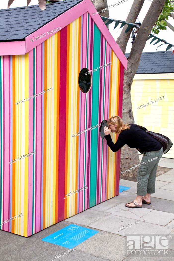 Stock Photo: A woman looks through the window of a beach hut, erected for the festival of Britain, The Southbank, London, England.