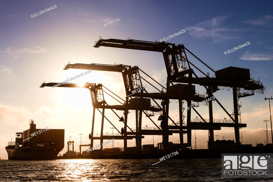 Photo de stock: Cargo container ship approaching three giant container cranes at the Port of Oakland intermodal container terminal.