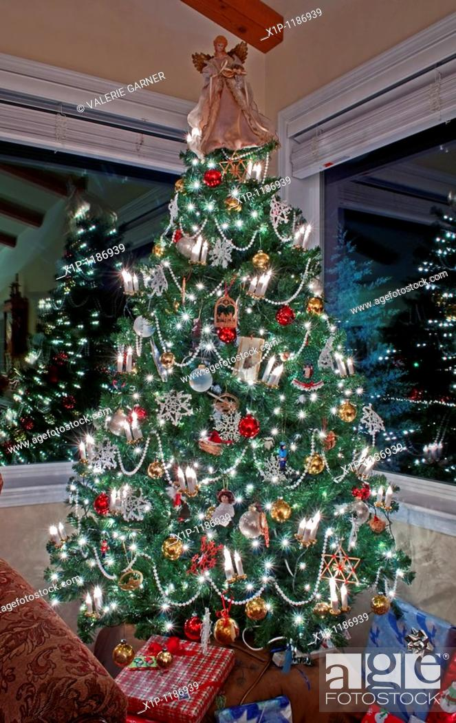 Stock Photo: This beautiful stock image is a vertical shot of an indoor lighted and decorated Christmas tree with two windows reflecting the lights and decor.