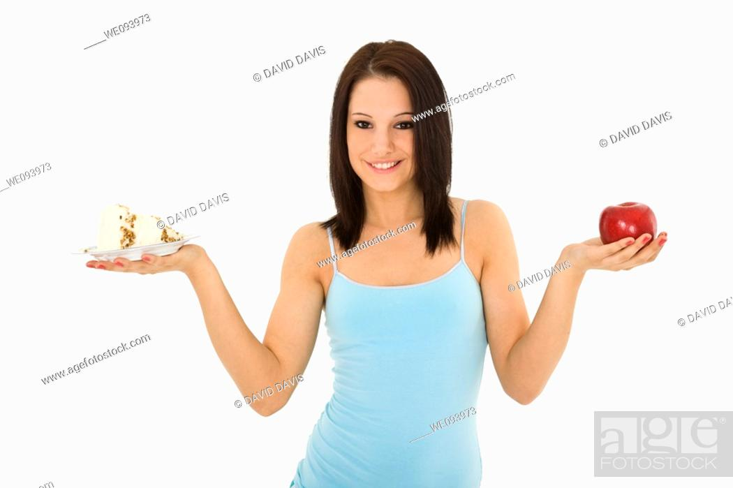 Stock Photo: Caucasian woman holding an apple and slice of cake trying to decide which one to eat.