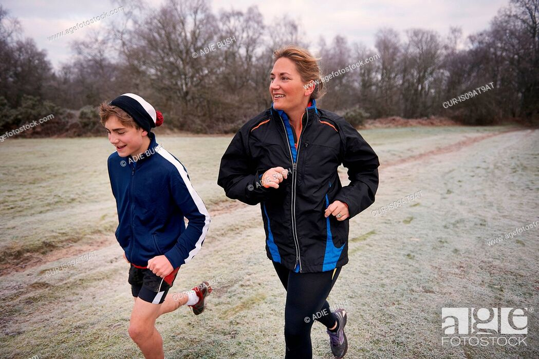 Imagen: Mother and son running on frosty grassland looking away smiling.