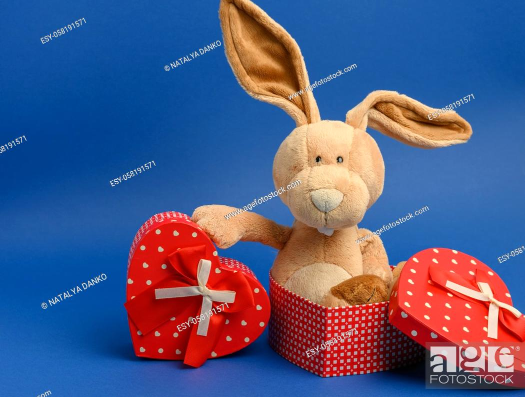 Stock Photo: cute plush rabbit holding a gift box tied with a red silk ribbon, blue background.