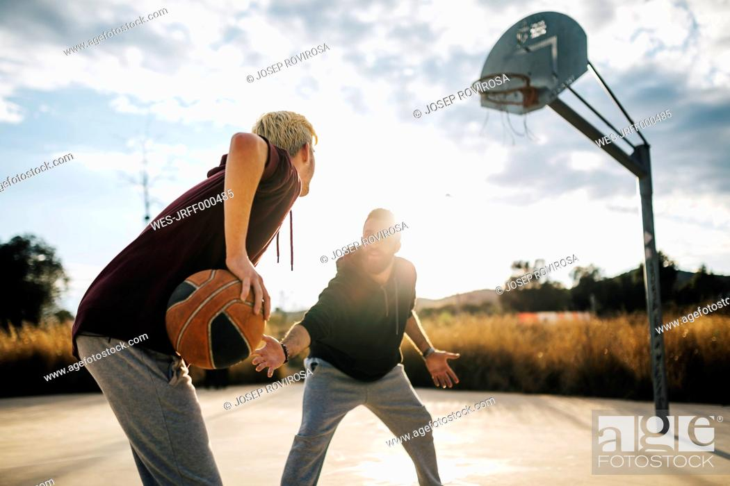 Stock Photo: Two young men playing basketball on an outdoor court.
