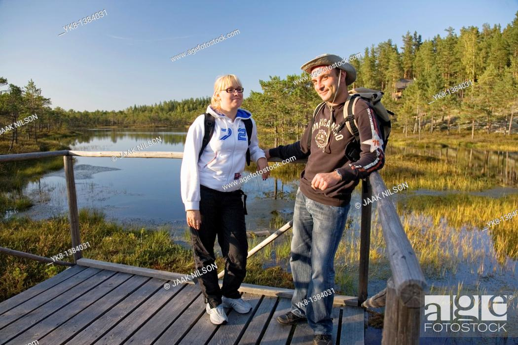 Stock Photo: Young Couple Standing on Wooden Boardwalk in Meenikunno Bog by Water, Estonia.