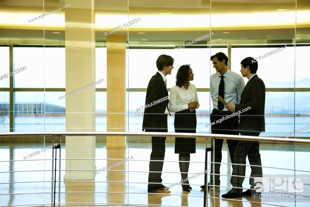 Stock Photo: Group of executives talking in corridor.