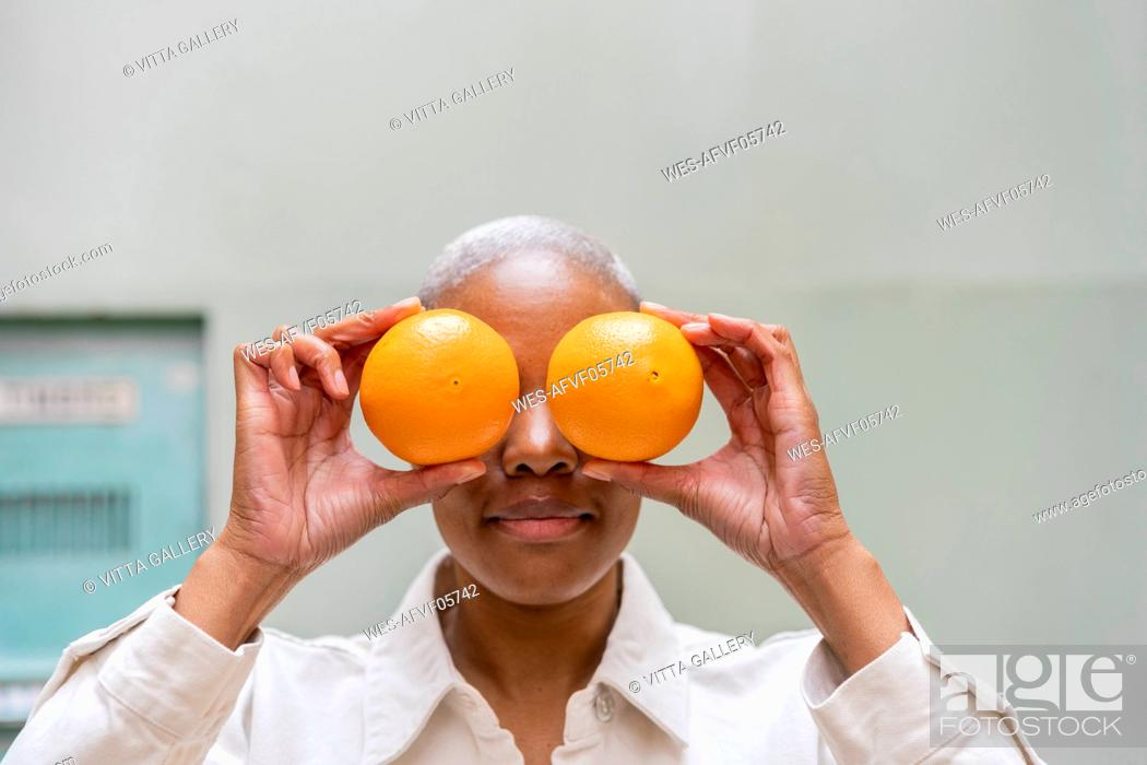 Stock Photo: Woman covering her eyes with oranges outdoors.