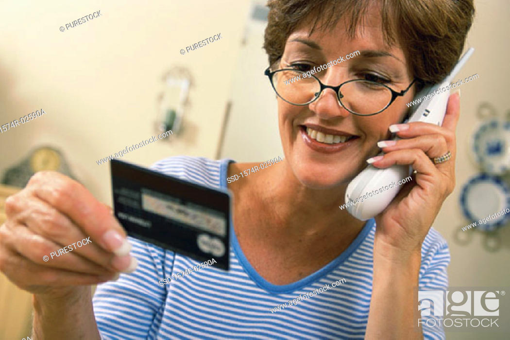 Stock Photo: Mid adult woman talking on a cordless phone holding a credit card.