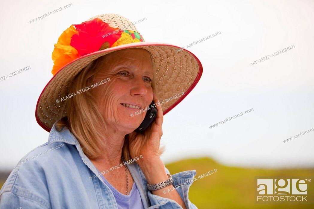 Stock Photo: Portrait of mature woman in a flower-decorated garden hat talking on cell phone, Kodiak Island, Southwest Alaska, Summer.