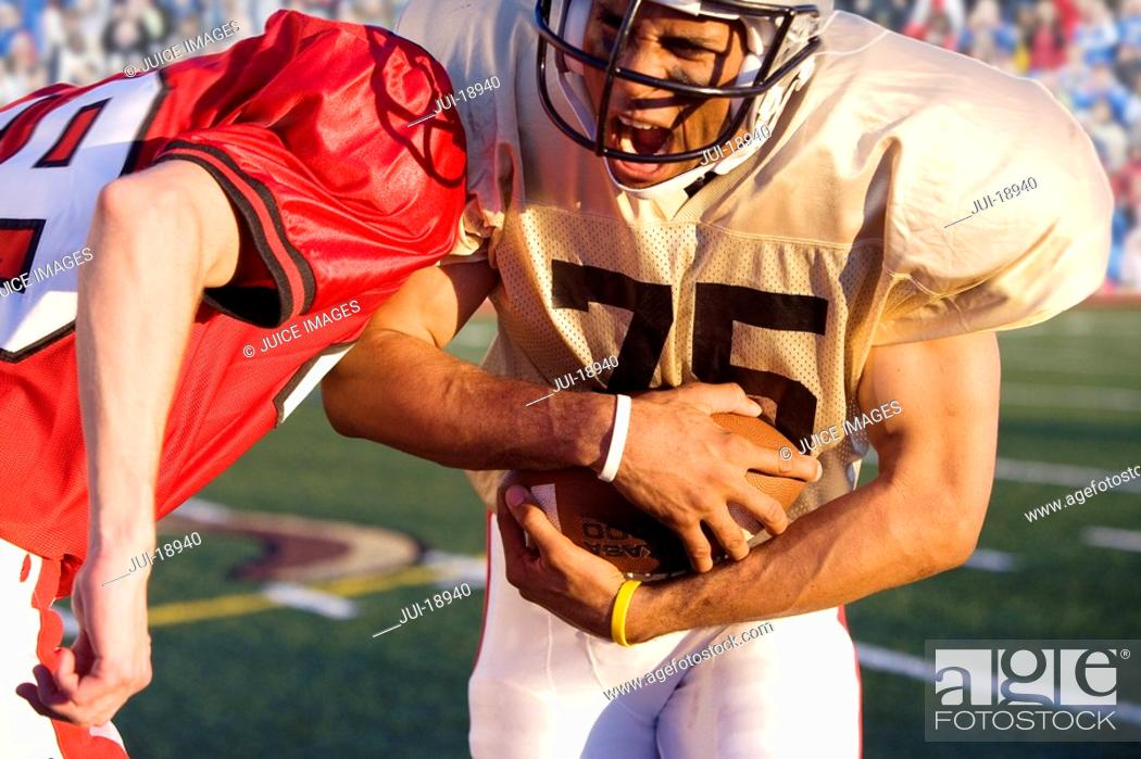 Stock Photo: Close up of running back with football running around defender.
