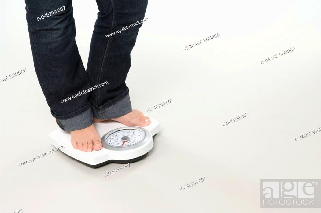 Stock Photo: A woman weighing herself.