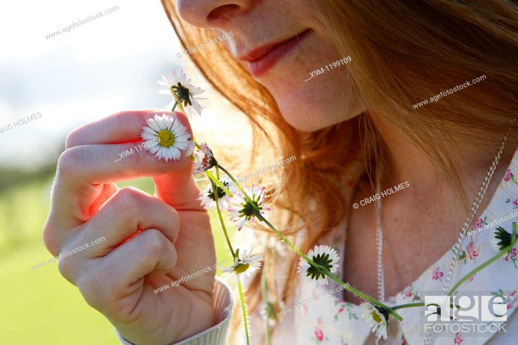 Photo de stock: Girl holding daisy chain outside in the sunshine.