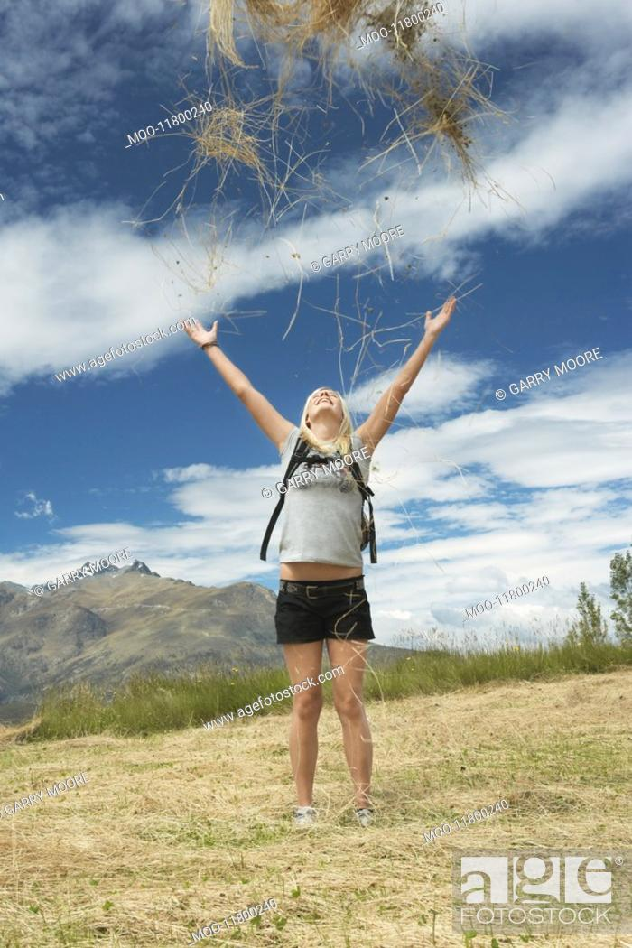 Stock Photo: Female hiker throwing grass into air in field.