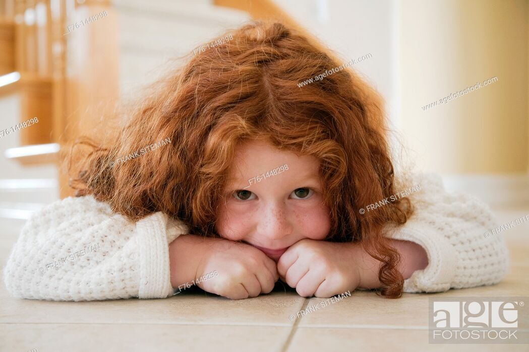 Stock Photo: Portrait of five year old girl with red hair lying on tiles on floor.