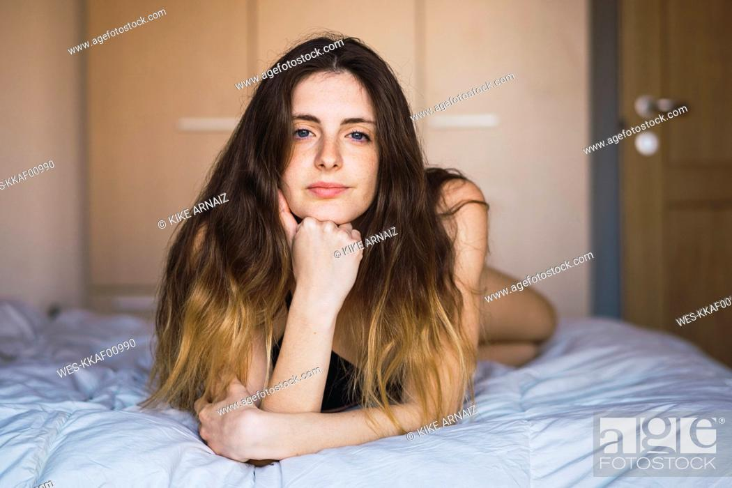 Stock Photo: Portrait of young woman hair lying on bed.