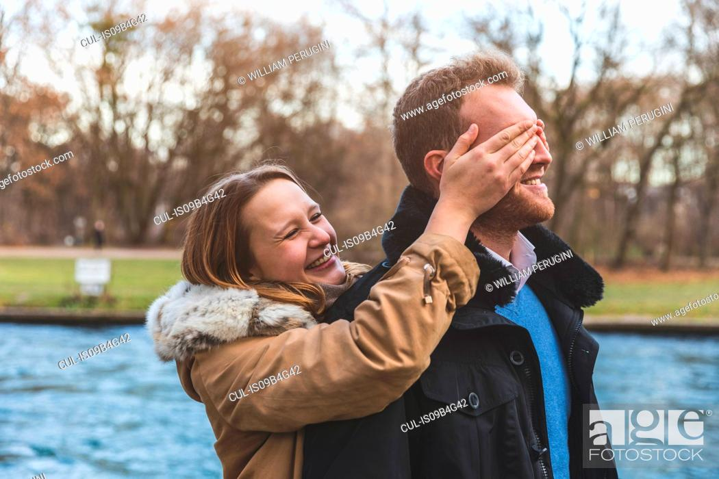 Stock Photo: Young woman covering boyfriend's eyes on park riverside.