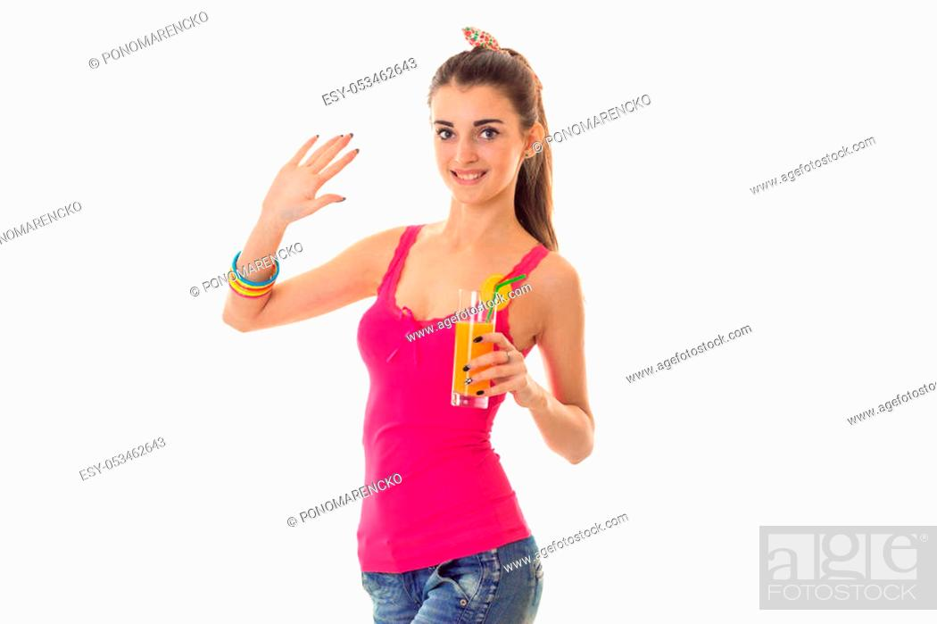 Stock Photo: cutie young brunette girl in light summer clothes with orange cocktail in her hands looking at the camera and smiling isolated on white.