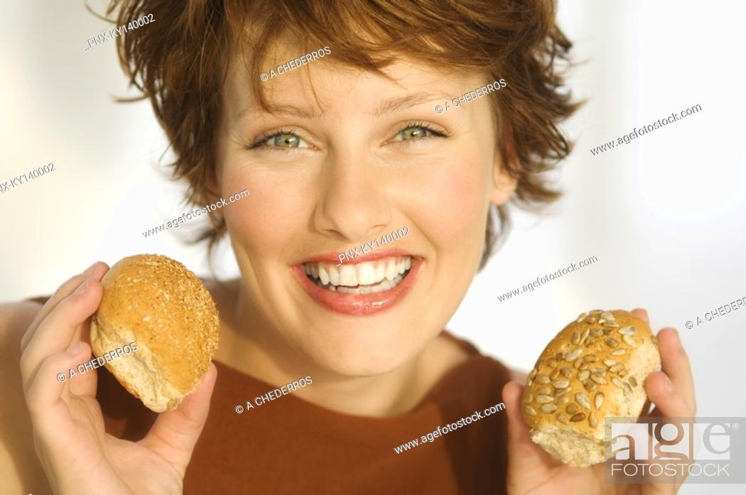Stock Photo: Portrait of smiling woman holding breads.