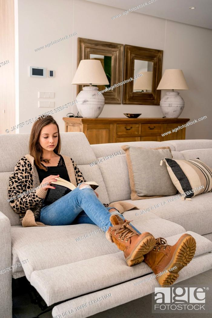 Stock Photo: Teenage girl reading book while relaxing on sofa at home.