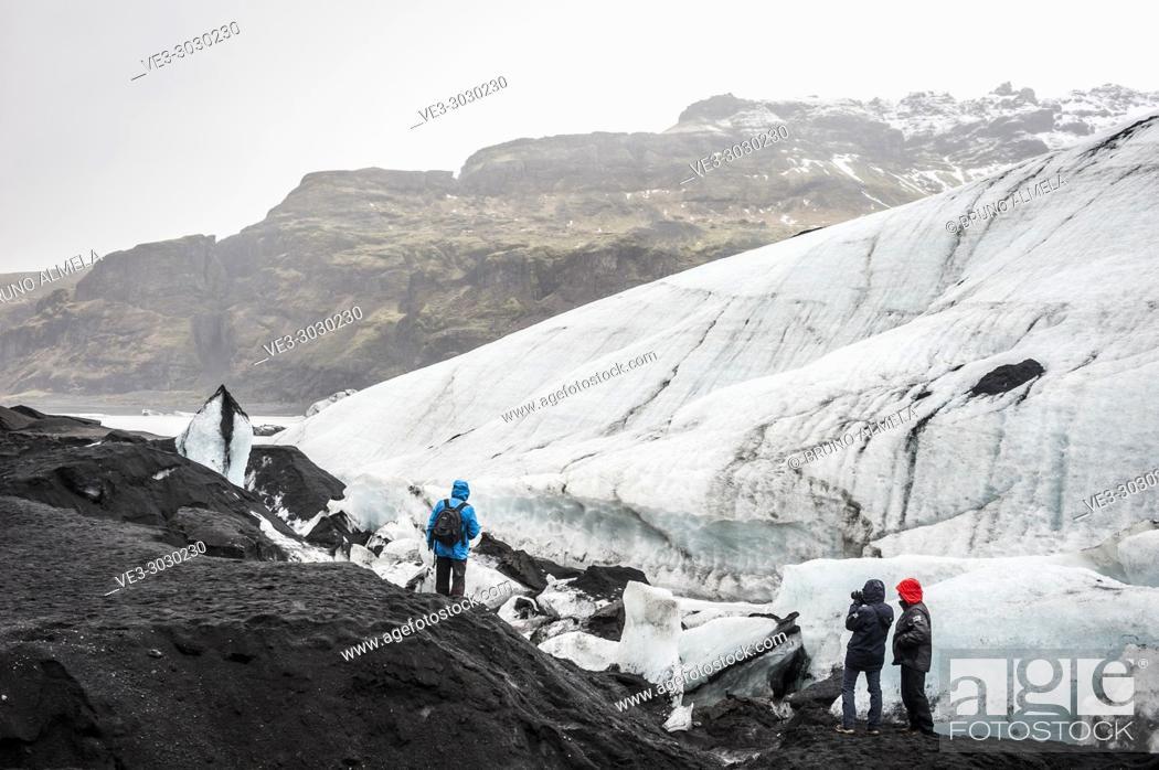 Stock Photo: Tourists visiting Sólheimajökull glacier (region of Suðurland, Iceland).