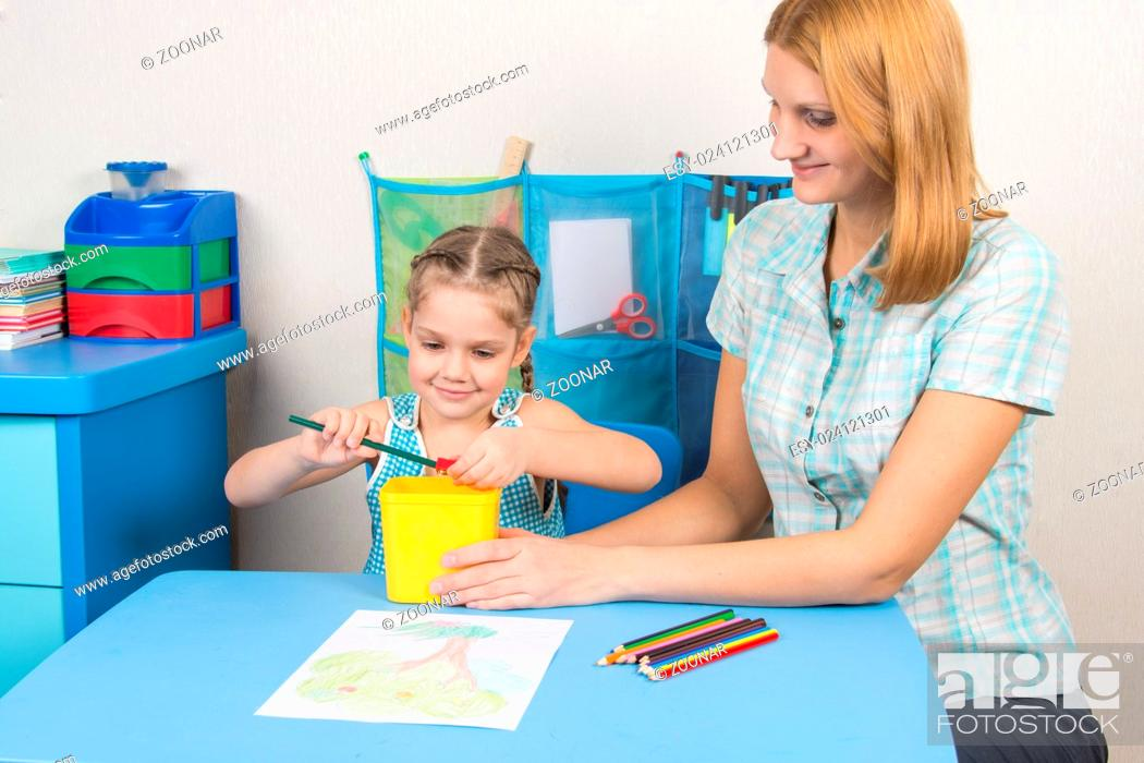 My mother helps the child to sharpen pencils, Stock Photo, Picture