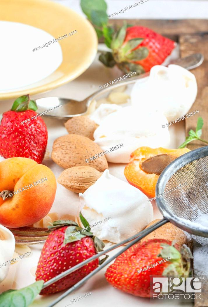 Stock Photo: Homemade meringue with apricots, strawberries, almonds and cream. Ingredients for dessert Eton mess.