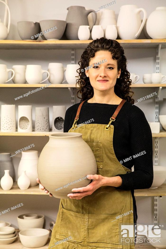 Stock Photo: Woman with curly brown hair wearing apron holding unfired spherical clay vase.